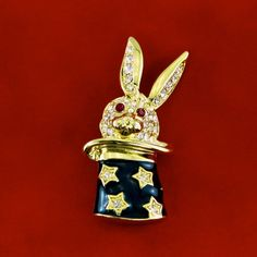 Surprise! It's jewelry magic when you wear this designer brooch. Cuter than a button, this rabbit is popping out with pave clear crystals and ruby red rhinestones for eyes. The hat is jet black enamel, adorned with stars. Sweet trick from Kenneth Jay Lane.