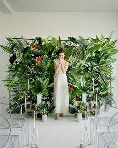 15 Gorgeous Indoor Wedding Backdrops To Try: a lush tropical leaf wall and leaves in concrete vases create bold modern tropical decor