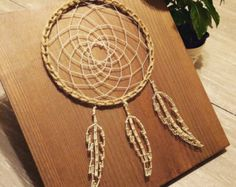 This dream catcher brings me back to summer with my feet in the grass and not a care in the world. Natural.  Made on a 11.5x12 piece of wood using a homemade stain. I used cream colored string for the feathers and inside the dream catcher and twine around the outer edge. Hanging hardware has also been added.  I will ship within one business day of ordering. All items are packaged to where they arrive in the same shape they left in. If you have any questions, please send me a message. I will…