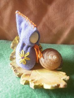 a little hazelnut gnome with stitched flower detail and orange trim sits on a clay leaf with a found (empty) snail shell.