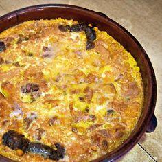 ARROZ CON COSTRA - Ingredientes:  1/2 kg pollo troceado, 1/2 kg costilla de cerdo, 1/2 kg gallina, 1 cabeza de ajo seco, 1 cebolla triturada, 1 tomate triturado, 1 morcilla seca, 200 g garbanzos secos, 450 g arroz Bomba de Pego, agua y aceite de oliva, colorante alimentario, 8 huevos.   Cocer las carnes, garbanzos y colorante. Preparar un sofrito con tomate, cebolla y ajos. Dorar el arroz, añadir la base y hornear 10 min. Batir huevos, añadir sobre la cazuela y hornear. FOTO: Rte L'Om de…
