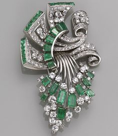 A diamond and emerald brooch  of scroll and spray design, three scrolling panels are the foundation for a cascading spray of European, transitional and single-cut diamonds, accented by rectangular and square-cut emeralds; estimated total diamond weight: 7.70 carats; mounted in eighteen and fourteen karat white gold.