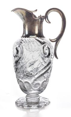 """A Victorian sterling silver-mounted """"Rock Crystal"""" glass ewer by John Grinsell & Sons, 1892 The body decorated with marine motifs, on an oval scalloped foot."""