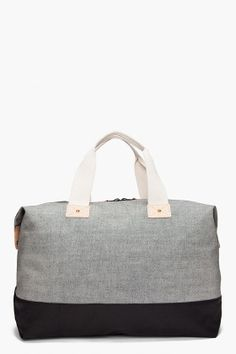 Rag & Bone. Large canvas duffle bag in grey with solid black contrast. Beige leather trim. Leather patch at front corner. $195
