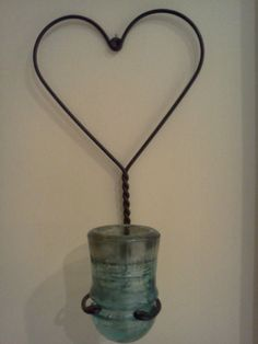 Old Rug Beater with glass insulator as candle holder! Ingenious.