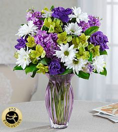 Mothers Day Flowers - FTD Loving Thoughts Bouquet - Purples in shades from pale pastels to plum pop perfectly among green alstroemeria and white daisy poms. For any Mom that has a passion for the calming, peaceful, mysteries of purple, this bouquet is made to order and is sure to be long-remembered. This brilliant gathering of stock, lisianthus, daisy poms, roses (in Better, Best and Exquisite) is hand-arranged by an FTD artisan florist in a heavy, lilac-hued heirloom quality glass vase.