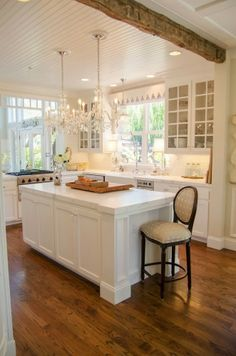 Sleek and modern appliances combined with classic beams and white marble countertops make for a timeless kitchen combination