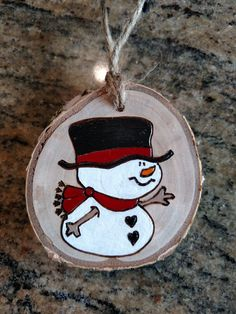 Snowman wood burned ornament. These ornaments are made out of white birch wood gathered from fallen limbs on our (and our extended familys) property. No trees are cut down to make my ornaments. Painted portions of this ornament are sealed with a glossy finish. Approximate