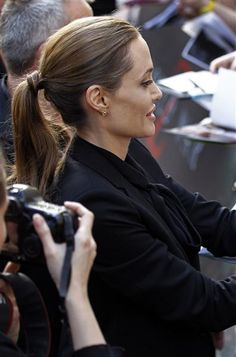 Hairdos and Don'ts. Angelina Jolie, wrapped her hair around her ponytail holder to make it more elegant. I love doing this with my hair!