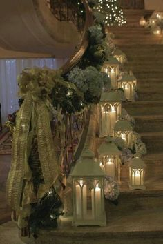 Christmas banister decorations - the abundance of the ribbon and swag along with the number of lanterns makes this so beautiful... And so impractical with kids climbing the stairs! One day!!!