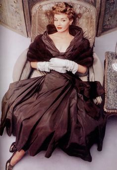 Vogue Magazine, October 1, 1948. Model in a made-to-order chocolate brown taffeta gown by Mark Morning, worn with a matching Baum Martens fur shrug and bronze Delman slippers. Photo by John Rawlings.