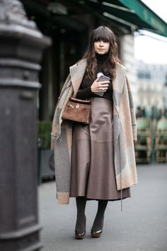 Chic Street Style From Paris Fashion Week - Miroslava Duma wearing a brown leather midi skirt, suede cross body bag + neutral color-blocked wool coat