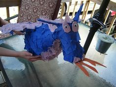 """A homemade dragon pinata is the perfect activity for a dragon or kights party theme. With these instructions, you can create a custom party decoration that kids can take turns at """"slaying"""" when it's time to crack it open.: Homemade Dragon PinataGather Your SuppliesCut the StripsAssemble the Head, Neck and TailMake the PasteDip Strips and ApplyPop Balloon and FillPatch the HoleCover with Tissue PaperAdd Wings, Horns and SpikesAdd Eyes and Fire"""
