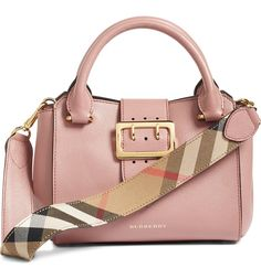 This small Burberry satchel in dusty pink makes a major style impact with oversized, logo-etched hardware and an optional guitar shoulder strap lined with Burberry's signature check.