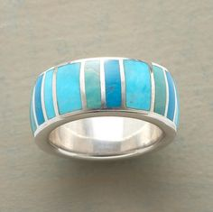 """A blue-to-green spectrum of turquoise encircles the finger inlaid in sterling silver. Exclusive. Whole sizes 5 to 9. Stone color will vary. 3/8""""W."""