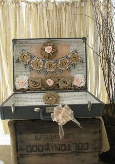 Vintage suitcase card holder                                               If you're planning a shabby chic wedding, consider this decoupage vintage suitcase as a card holder. The Shabby Chic Wedding combines book pages, scrapbook paper, vintage postcards, lace and handmade flowers to create this rustic masterpiece. Matching flower-girl baskets and ring-bearer pillows are available.