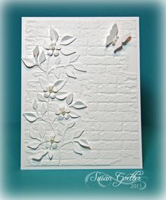 "1. Brick wall embossing folder: Tim Holtz.      Adhered directly to card base.   2. Stems & leaves: Sizzix die. Adhered in spots      so parts raised slightly. 3. Small blooms: EK Success punch 4. Butterfly: Martha Stewart punch.  5. Small pearl: Center of each bloom, butterfly.   6. Clear glitter: To butterfly (color doesn't show     in photo.),  7. Made for challenge: ""Less is More, White on     White."" 8. Susan Goetter"