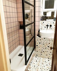 "Bathroom floor and vanity wall decorated with ""confetti"" terrazzo tiles. The..."