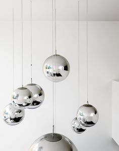"""Bruce worried about what to put in the double-height space above the kitchen table—–until he found these Tom Dixon–designed mirror balls. """"They were installed at random and when William came over that evening, he said, 'Fantastic, well done.' So we left them like that."""""""