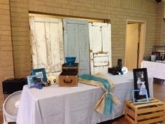Old repurposed doors as backdrop for wedding table vintage cameras and boxes for props on photo display with burlap runner