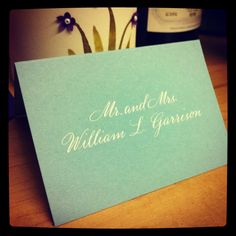 Copperplate calligraphy with white ink for an escort card sample.