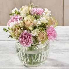 50% EXTRA FREE ROSES! Soft peach roses are arranged alongside pink carnations, fragrant white freesia and limonium to bring this beautiful bouquet together.