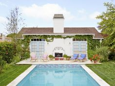 It's safe to say the Kandlers' pool, with its splashy lilac-and-turquoise tiling, isn't like any other on the block. The patio off the garage follows suit, trading run-of-the-mill chairs and loungers for vintage teak pieces, all bought at a flea market. Softened with pastel cushions, they look more garden party than pool party. Joseph's Coat roses and Boston ivy climb up the exterior, framing the seating area.