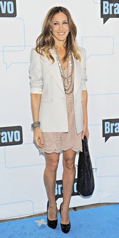 Sarah Jessica Parker in white Stella McCartney blazer and lace dress, worn with black heels, black bag, and layered necklaces and bracelets.