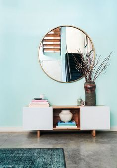 Living room with aqua colored walls, a round mirror, and a console table