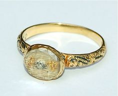 17th Century Skull Ring.     A fine example of a 17th century memento mori skull ring, dated 1699. The chased high carat gold shank is decorated with black enamel and terminates in a compartment containing a ground of woven hair overlaid with gold cipher initials JW and an enamel skull and crossbone device. The compartment is covered by a faceted crystal. The gallery of the ring is decorated with flutes of black enamel. To reverse, in naive italic script, is the inscription : obt Sept the 5…