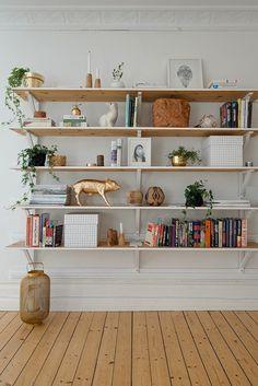 sol en planchers clair, étagère murale en bois et mur blanc