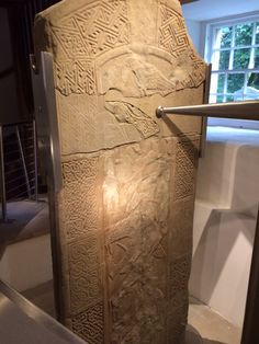 The Nigg Cross-Slab dating from late 8th century. The reverse shows David, identified by a sheep and a harp, wrestling with a lion. Hunting scenes appear above and below. During restoration of the slab in 2012-13 a missing piece was added and can be seen to the left of the steel support.