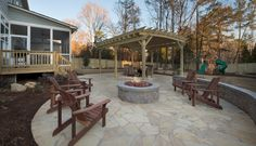 Stylish Outdoor Living Complete with Firepit and Stone Seating Area Overlooking the Kid's Play Area.