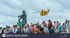 Download this stock image: Yellow RAF Sea King helicopter flies over crowds at Moelfre Lifeboat day on Anglesey, August 2014. - JB683P from Alamy's library of millions of high resolution stock photos, illustrations and vectors.