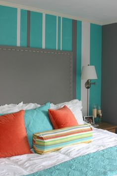 Wallcovering. Bedroom. Children's bedroom. Turquoise bedroom with striped walls. Striped wall paint. Orange pillows.