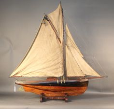 """Early 20th century """"Straight Line Racer"""" pond yacht.  A straight line racer is an English racing class for model yacht racing.  The model is rigged with a full suit of sails, brass hardware, set onto a wood cradle.  49"""" long x 10"""" wide x 49"""" tall Estimate: 2500 - 3500"""