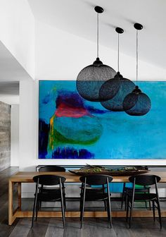 A vibrant painting hangs in the dining room of this Templestowe house designed by Christopher Elliott Design where it adds life to the white walls and wood tones.