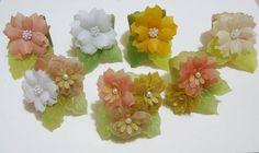 Porta-guardanapos em papel vegetal tingido, composto de 3 flores com centro em pérola ou cristal. Pedido mínimo: 12 unidades. R$ 8,00