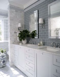 interior design bathroom: white double vanity with marble top, grey subway tiles, marble tiles, wall sconces