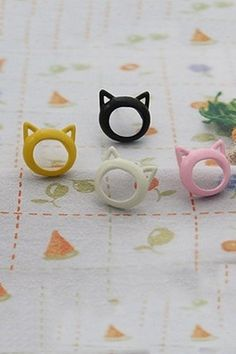 Earrings crafted in plastic, featuring the cat face design with cut out detail, and a pin fastening to reverse.