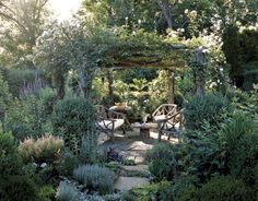"""Secret Garden  With a structure to grow on, plants can create living walls that offer privacy and seclusion. Here, a cedar arbor boasts a dense covering of roses that forms a natural """"roof,"""" while a boxwood shrub anchors the base of each column. The result is an intimate seating area that can be used for relaxing or dining."""