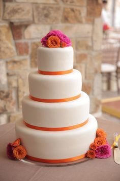 Orange + pink wedding cake - four-tier white fondant frosted wedding cake with orange ribbon and hot pink and orange flowers {Pepper Nix Photography}