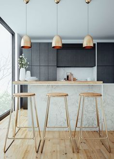 Modern kitchen with marble, black cabinets, bronze pedant lamps and gold bar stools
