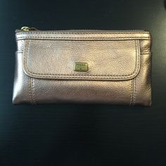 "NWT FOSSIL EMMA LEATHER CLUTCH NWT. FOSSIL EMMA LEATHER CLUTCH IN PALE ROSE METALLIC. Beautiful leather. Zippered and snap closures. Two snaps makes it easy to close a fuller wallet. Front exterior snap pocket and zip pocket. Fossil name plate on exterior. Interior 1 zip pocket, 1 slot pocket, ID slot, 12 credit card slots. Dimensions: 7.5""L x 4.25"" H x 0.5""W. Fossil Bags Clutches & Wristlets"