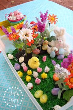 Easter themed sensory tub with all sorts of cute Easter goodies like chicks, eggs, spring flowers and of course, the Easter Bunny.