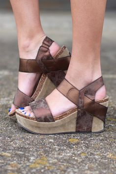 The sandal wedge of the season! This designer inspired look is super comfortable and features a stretchy strap for easy off/on. Metallic strap that works well with the color of the sandal. Brown in co