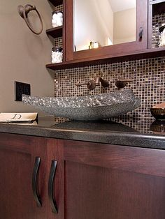 Cherry cabinets are  great feature in every kitchen or bathroom. It perfectly complements with bronze faucet and unique bathroom sink.