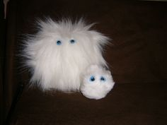 Pygmy Puffs! The large one was what I made special for my son. The smaller ones I made as a gift for each guest. They came in white, brown, and pink. I used large poms and eye sets that just pin into the pom. I made cute little adoption cards and Weasley boxes for each of them.
