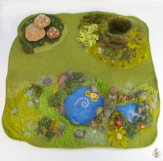 "This play mat is 18""x18"". It is made with a thick wool base and has wool roving, yarn, pre-felt, felt and silk components. It is made by needle felting, hand sewing and some glue. The wool and silk are home dyed. The base is about 1/4"" thick."