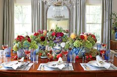 Lively Brights - Christmas in the Dining Room - Southernliving. This elegant tablescape makes the most of cheery flower arrangements in a series of blue-and-white vases. The blue-and-white theme keeps the table looking clean and streamlined, but the flowers add vibrancy and playfulness with lime, magenta, ruby, and yellow hues.